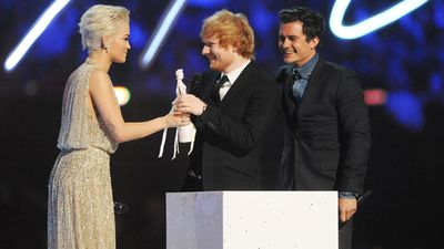 Rita Ora receives her award from Ed Sheeran and Orlando Bloom. (Getty)