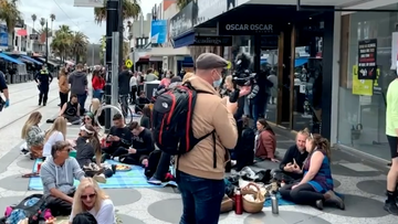 Dozens of protesters lined a St Kilda dining strip this afternoon to demonstrate against rules banning unvaccinated people from entering venues and shops.