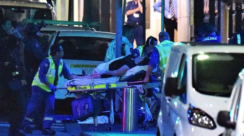 Paramedics begin wheeling out the injured. (AAP)