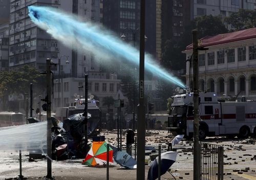 An armoured police vehicle sprays blue-dyed liquid during a confrontation with protesters at the Hong Kong Polytechnic University in Hong Kong. A Hong Kong police officer was hit in the leg by an arrow  as authorities used tear gas and water cannons to try to drive back protesters occupying a university campus and surrounding streets