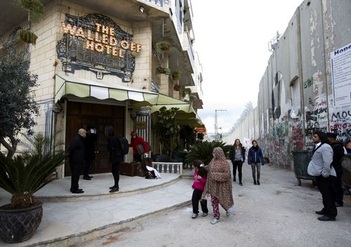 "People pass by the ""The Walled Off Hotel"" and the Israeli security barrier in the West Bank city of Bethlehem. The nine-room hotel claims to have the worst views in the world."