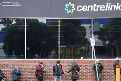 People are seen queuing outside a yet to open Centrelink office in Heidelberg, Melbourne, Tuesday,
