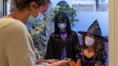 Children dressed in halloween costumes Trick-Or-Treating. They wear face masks. Covid-19 times. New normal concept.