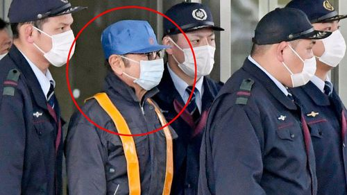 Former Nissan chairman Carlos Ghosn wears a costume of a blue hat and face mask as he walks free from the Tokyo Detention House, where he was held for 108 days
