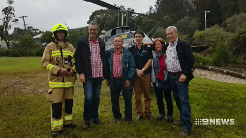The pilot, the relieved tourists and a firefighter pose at the scene after the ordeal. (Supplied)