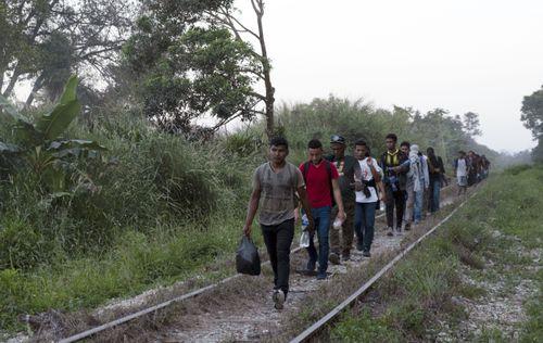 Para migran berjalan di rel kereta api dalam perjalanannya dari Amerika Tengah ke perbatasan AS di Palenque, negara bagian Chiapas, Meksiko, Rabu, 10 Februari 2021.