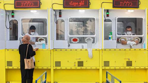 A woman is tested by a healthcare worker for the coronavirus at a mobile testing station, in east Jerusalem.