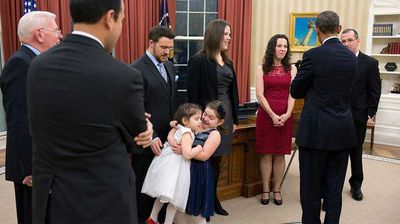 As President Obama speaks with departing staffer Mary Wall, two sisters take part in some hijinks. (Flickr/White House)