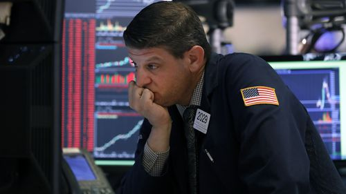 Trader Michael Gallucci works at his post on the floor of the New York Stock Exchange today. Trading was halted as stocks plummeted on the back of coronavirus concerns.