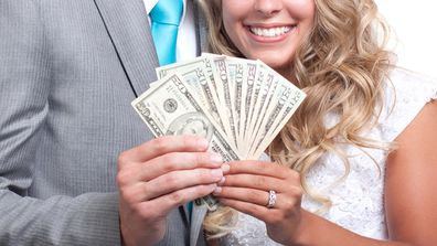 Bride and groom holding money