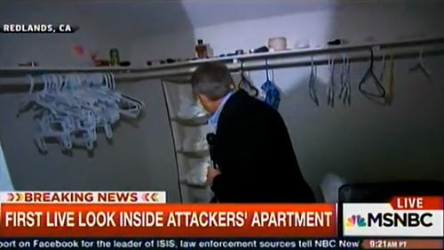 Reporter Kerry Sanders looks through the wardrobe inside the alleged shooters' apartment. (MSNBC)