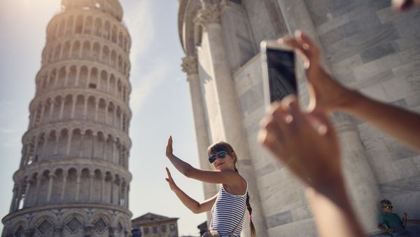 Woman taking photos at the Leaning Tower of Pisa