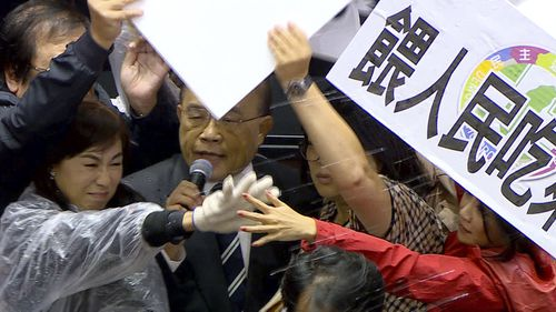 In this image made from video, lawmakers fight during a parliament session in Taipei, Taiwan, Friday, Nov. 27, 2020.