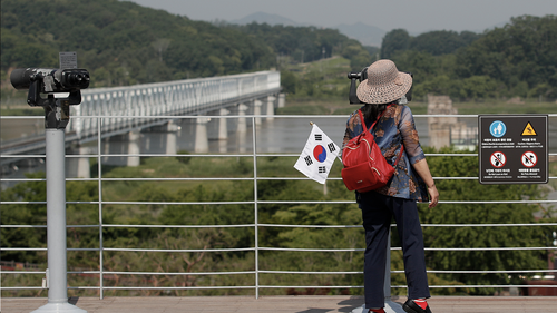 A visitor carrying a national flag uses binoculars to view the northern side at the Imjingak Pavilion in Paju, South Korea, Tuesday, June 9, 2020. North Korea said Tuesday it will cut off all communication channels with South Korea as it escalates its pressure on the South for failing to stop activists from floating anti-Pyongyang leaflets across their tense border. (AP Photo/Lee Jin-man)
