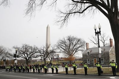 Officers salute the passing funeral cortege in Washington DC