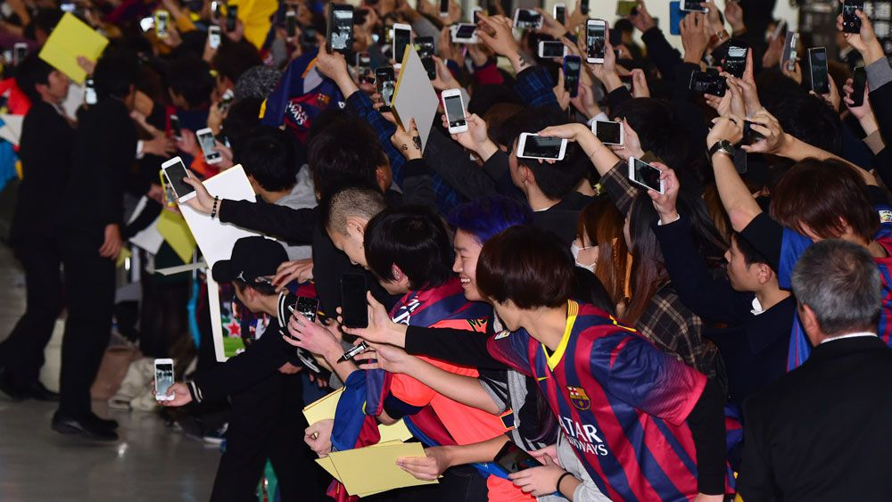 Barcelona fans await their heroes in Japan. (AFP)