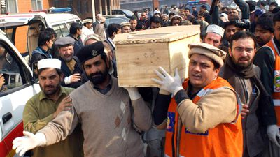 Pakistani volunteers move the coffin of a student from a hospital. (Getty Images)