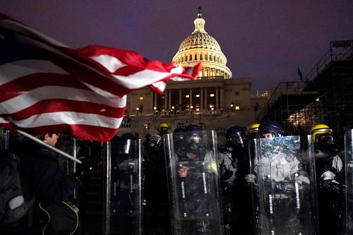 Police stand guard the day after riots at the US Capitol.