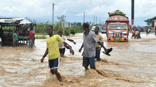 People try to cross the overflowing La Rouyonne river in the commune of Leogane, south of Port-au-Prince, Haiti, on October 5, 2016.