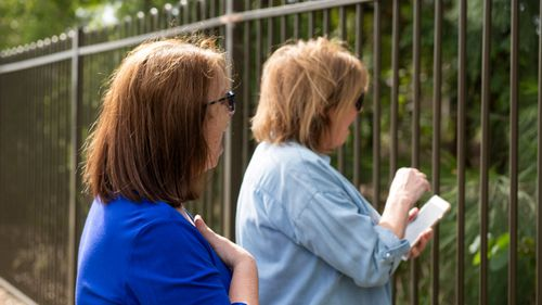 Sisters Joyce Parker and Mary Watson wave to their mother Alice Bacon on April 29.