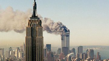 The World Trade Centre burns behind New York City's Empire State Building, Sept. 11, 2001.