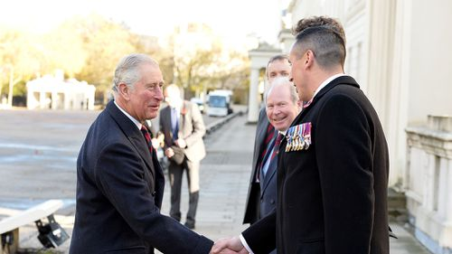 The Prince of Wales is greeted by Colonel Tom Bonas and WSM Dean Morgan as he arrives at the Guards' Memorial at the Guards' Chapel, Wellington Barracks, London. (AAP)