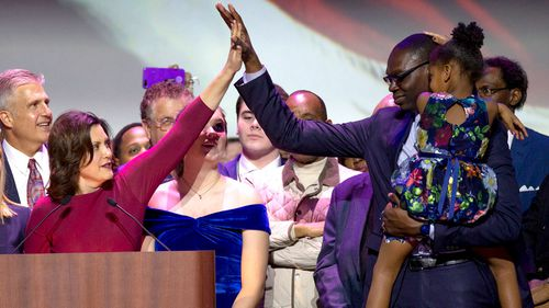 Democrat Gretchen Whitmer high fives Garlin Gilchrist II as she declares victory over Bill Schuette at their election night party during the 2018 mid-term general election at the Motor City Casino Hotel in Detroit, Michigan.