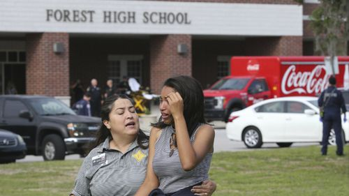 A student is comforted by a school official. (AP)
