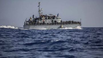 A photo released by the Libyan Coast Guard shows a ship with migrants off the coast of Libya, June 24, 2018.