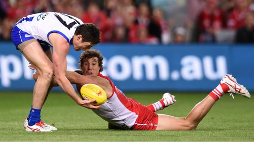 Nathan Grima and Kurt Tippett compete for a loose ball in what was a tough night for North Melbourne's defenders. (AAP)
