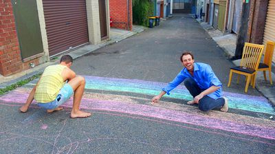 The removal of the crossing sparked a city-wide protest - James Brechney colours in the first chalk rainbow in a Surry Hills laneway. (Facebook)