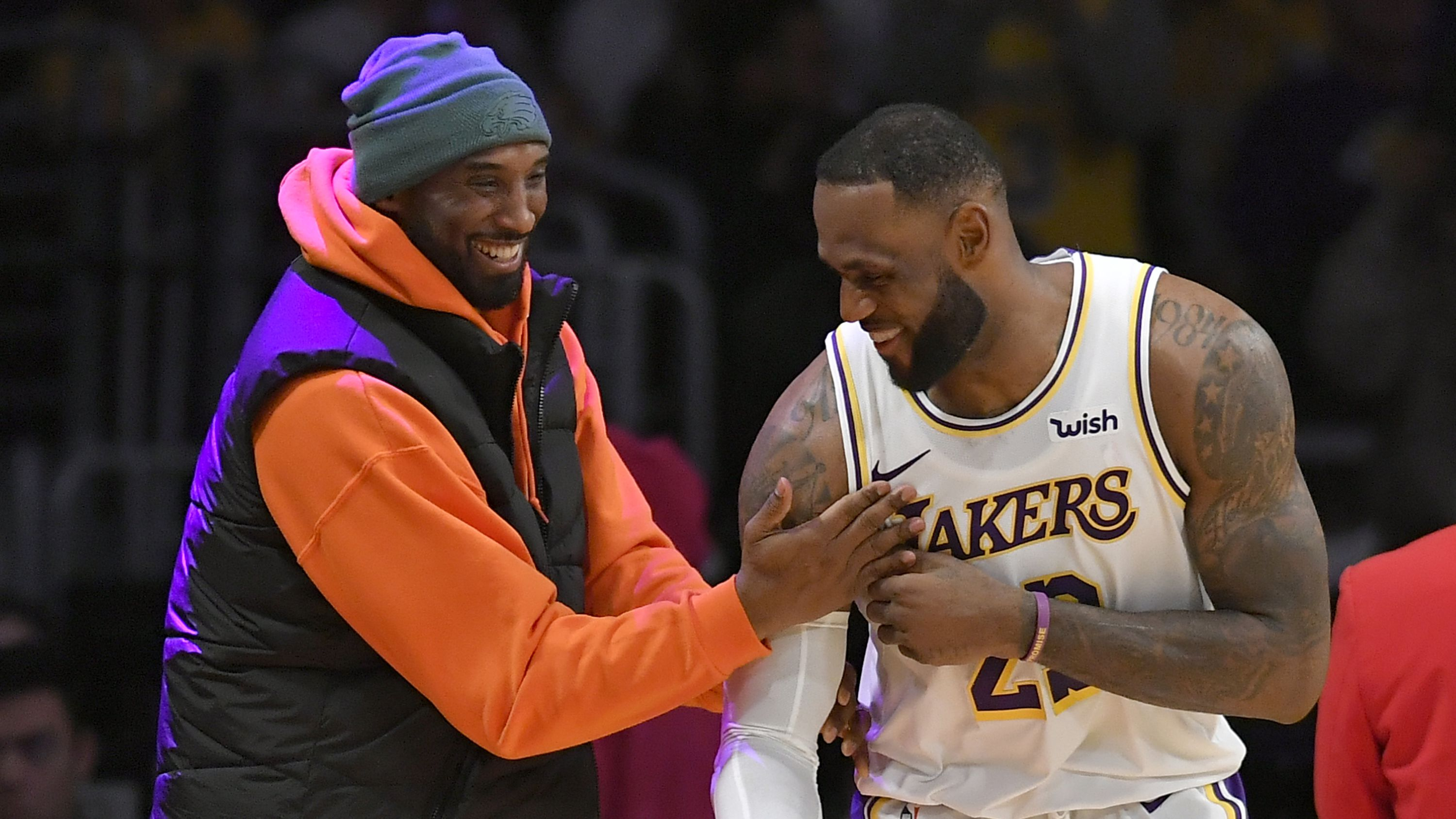 LeBron James of the Los Angeles Lakers has a moment on the sideline with former Laker Kobe Bryant.