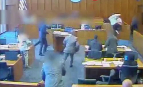 He then launches himself over the witness box towards the shackled witness. (Supplied)