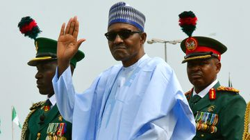 Nigerian President Muhammadu Buhari waves to the crowd during the 58th anniversary celebrations of Nigerian independence, in Abuja, Nigeria. Nigeria's president on Sunday Dec. 2, 2018, took the extraordinary step of denying rumors that he died and was replaced by a body double, telling the country that he is alive and well.