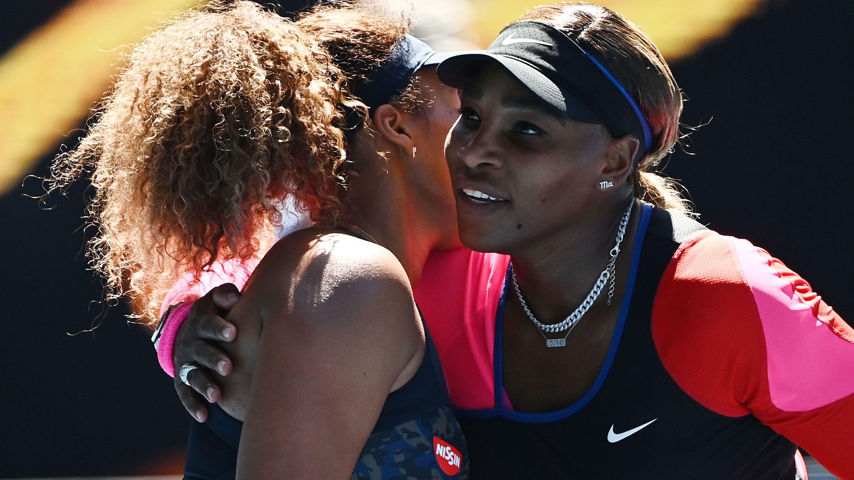Naomi Osaka is embraced by Serena Williams.