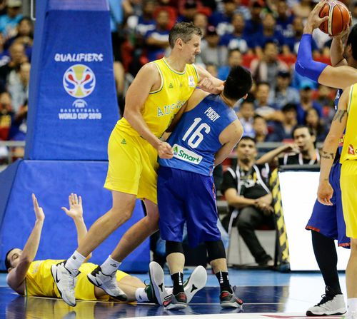 Christopher Goulding lies on the ground as Daniel Kickert of Australia elbows Roger Pogoy of the Philippines during the FIBA Basketball World Cup 2019 Group B qualifier match. Image: EPA