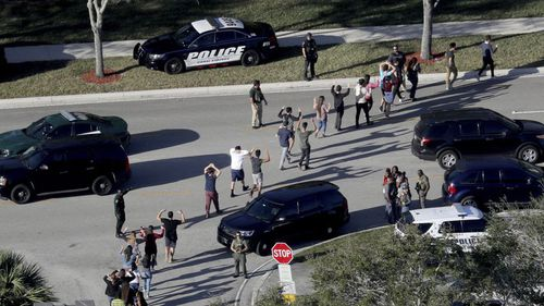 Students are led from Marjory Stoneman Douglas High School after the shooting. (AP/AAP)