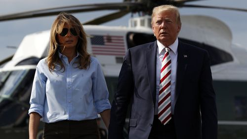 President Donald Trump, with first lady Melania Trump, walks towards the media.