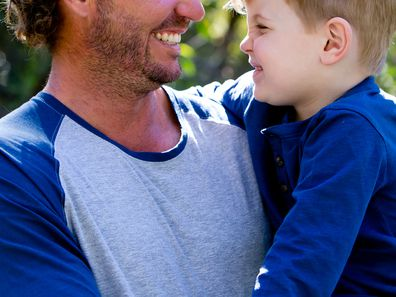 Father holding young son outdoors in sunlight in park - looking away from camera