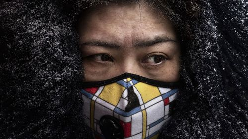 A Chinese woman wears a protective mask as she shops in a market on February 6, 2020 in Beijing, China.