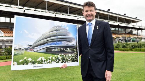 VRC Chairman Michael Burn poses for a photo with an artist impression of the proposed members grandstand front of the 93-year-old existing structure. (AAP)