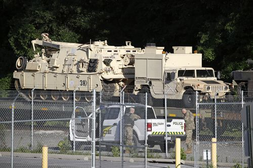 Military police stand military vehicles on a flat car in a rail yard, Monday, July 1, 2019, in Washington.