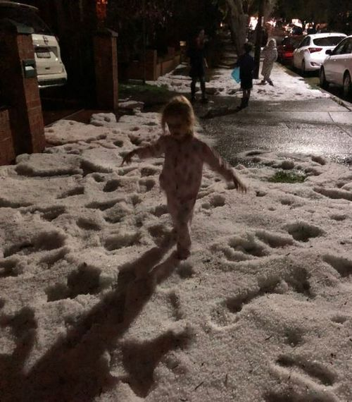 Kids play in the 'snow' as large hail blankets Sydney.