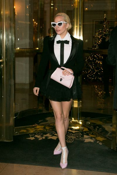 Lady Gaga in a tuxedo mini-suit clutching a customised bag from the Cambridge Satchel Co. emblazoned with 'Joanne' and Cassadei pumps.