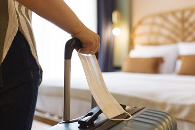 Woman with face mask and suitcase in the hotel room, close up.