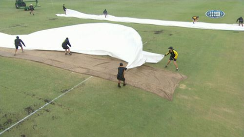 Workers struggled to cover the pitch as rain bucketed down at the WACA yesterday. (9NEWS)