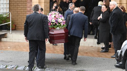 Ms Herron's casket was adorned with pink and white flowers.