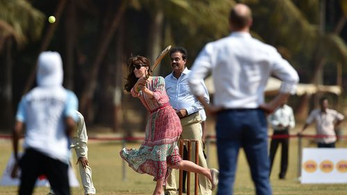 The Duchess of Cambridge bats as the Duke of Cambridge looks on during a charity cricket match at the Oval Maidan recreation ground in Mumbai. (AAP)
