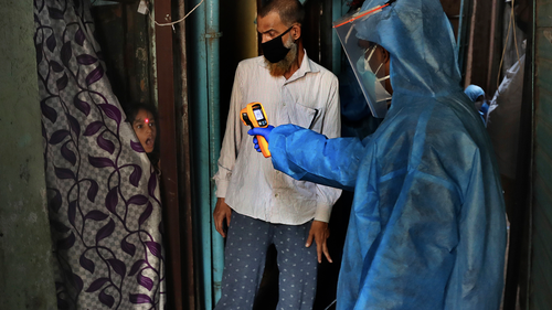 In this Monday, April 13, 2020, file photo, a doctor checks the temperature of a girl in Dharavi, one of Asia's largest slums, during lockdown to prevent the spread of the new coronavirus in Mumbai, India.