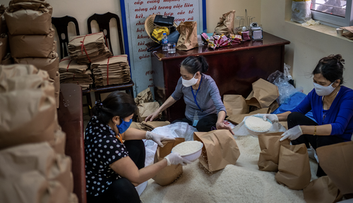 "HANOI, VIETNAM - APRIL 17: Volunteers wear face masks amid concerns of the spread of the coronavirus disease (COVID-19) while preparing free rice bags on April 17, 2020 in Hanoi, Vietnam. Several self-catering ""rice ATMs, or rice dispensers, have been launched providing free rice to low-income earners to survive the pandemic."